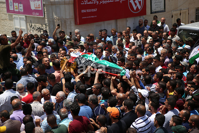 Mourners carry the body of 21-year-old Palestinian Abdallah Ghanayem, during his funeral in the village of Kafr Malik, northeast of Ramallah on June 14, 2015. An army spokesman said that the Palestinian had died after he threw an incendiary device at a jeep and the vehicle overturned on him. Palestinian security sources said, Israeli soldiers killed Ghanayem by hitting him with their jeep during clashes near Ramallah in the occupied West Bank. Photo by Shadi Hatem