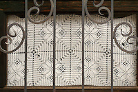 White lace window curtain, San Miguel de Allende, Mexico. San Miguel de Allende is a UNESCO World Heritage Site.