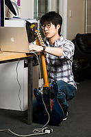 Sang-won Leigh works on the Guitar Machine device in the Fluid Interfaces Group lab space at MIT's Media Lab in Cambridge, Massachusetts, USA, seen here on Tues., April 25, 2017. Sang-won Liegh is a grad student and research assistant in the Fluid Interfaces Group, led by Pattie Maes. The device seen here is part of the Robotic Symbiants project in the group, which augment human function. In this case, the device acts as additional fingers on a guitar fretboard, allowing a player to play chords that have not previously been possible. The device now works with pre-programmed movements, but Sang-won Leigh said that in the future, a similar device could adjust its playing in realtime to harmonize with what the human player is doing.