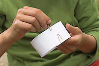 Kinder gießen Tierspur aus Gips, Junge formt aus Karton mit Büroklammern einen Ring