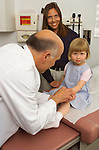 older, elder male doctor examining hand of 3 year old girl while mother looks on
