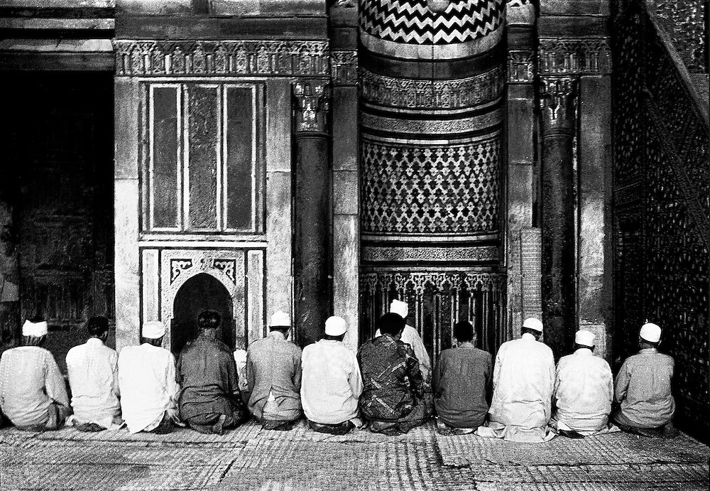 Twelve Egyptian men at prayer before the qibla of the mosque