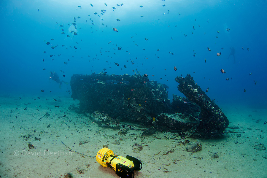 Two divers (MR) with underwater scooters explore a WW II landing craft off the coast of South Maui, Hawaii.