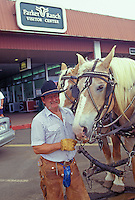 A man, a staff member, wearing cowboy gear and standing with bridled horses at the Parker Ranch visitor center on the Big Island