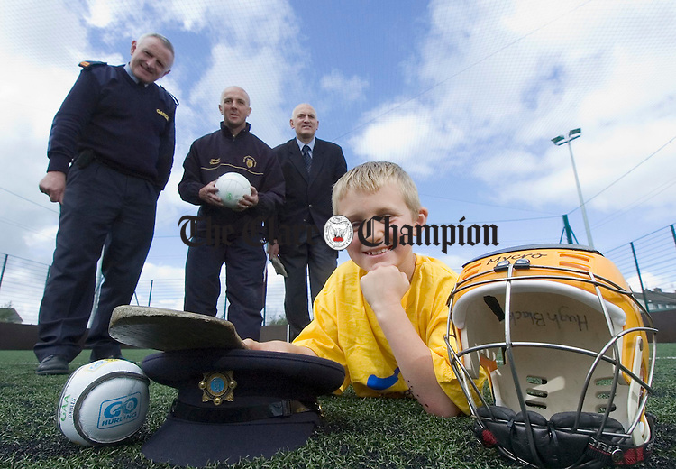 Inspector Michael Gallagher of Ennis Gardai, Joe Gleeson, Ennis Urban Board and Pat Hanrahan, principal Scoil Criost Ri, Cloughleigh, with sportsman Colin Reidy, a pupil, at the launch of a coaching programme in conjunction with the Ennis Gardai, Scoil Criost Ri and the GAA Urban Board. Photograph by John Kelly.