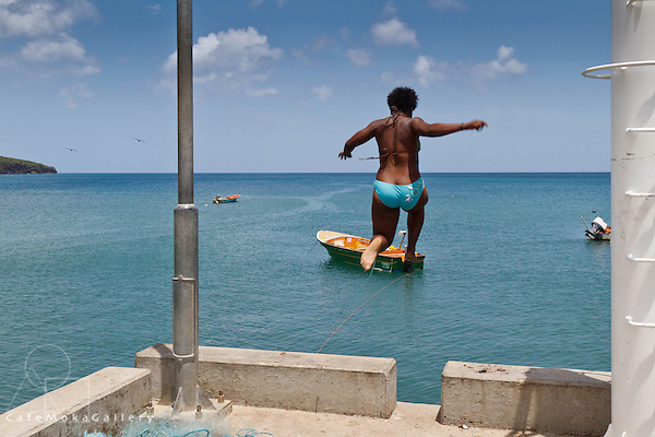 Woman jumping off the jetty into the sea at Anse La Raye, St Lucia