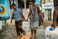 Neighbours help each other carry the 20 litre water cans home after buying safe water from the iJal station in Peddapur, a remote village in Warangal, Telangana, India, on 22nd March 2015. Safe Water Network works with local communities that live beyond the water pipeline to establish sustainable and reliable water treatment stations within their villages to provide potable and safe water to the communities at a nominal cost. Photo by Suzanne Lee/Panos Pictures for Safe Water Network