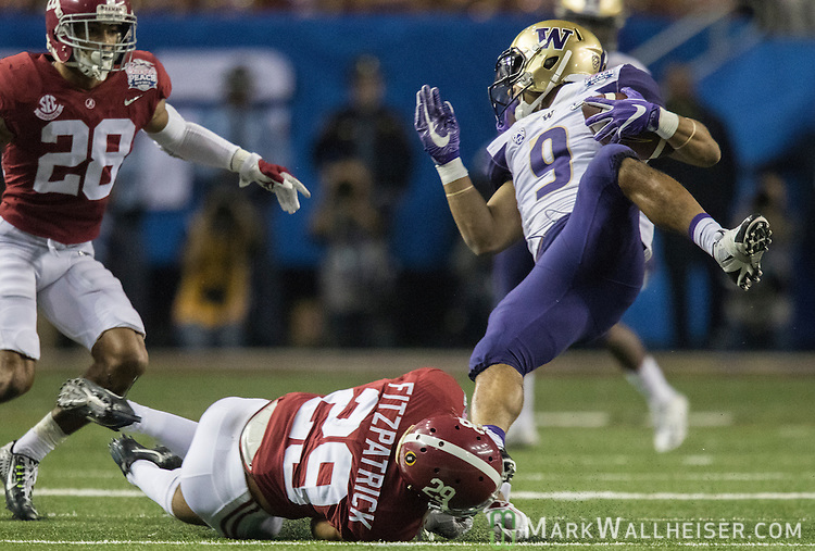 Washington tailback Myles Gaskin (9) gets tripped up by Alabama defensive back Minkah Fitzpatrick (29) in the second half of the 2016 Peach Bowl at the Georgia Dome in Atlanta, Georgia on December 31, 2016. Alabama defeated Washington 24-7.  Photo by Mark Wallheiser/UPI