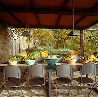 Under a wooden awning on the terrace a table displays produce from the adjacent vegetable garden in local tin-glazed ceramic bowls