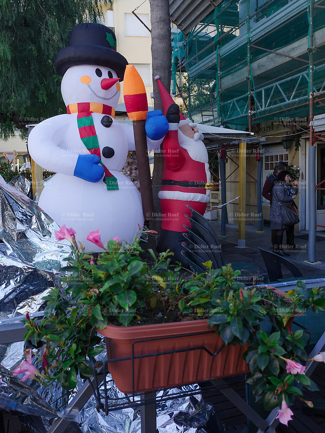 Italy. Liguria Region. Bordighera. Two inflatable dolls of Santa Claus and a snowman. A couple looks at a shop's window. Scaffolding on a building. Cyclamen flowers. 27.12.16 © 2016 Didier Ruef