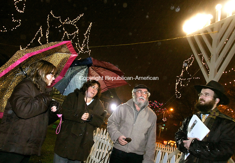 WATERBURY, CT-- 11 DECEMBER 2007--121107JS01-Rabbi Joseph Eisenbach of the Chabad Lubavitch of Northwest Connecticut, right, leads Stephanie Borowski, 12, of Naugatuck, Paula Borowski and Alain Levy of Thomaston in song during the second to last night Hanukkah Tuesday on the Green in Waterbury. Rabbi Eisenbach also handed out toys to local children. <br /> Jim Shannon/Republican-American