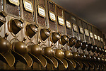 A row of 14 brass, coffee bean dispensers photographed in a city coffee shop.