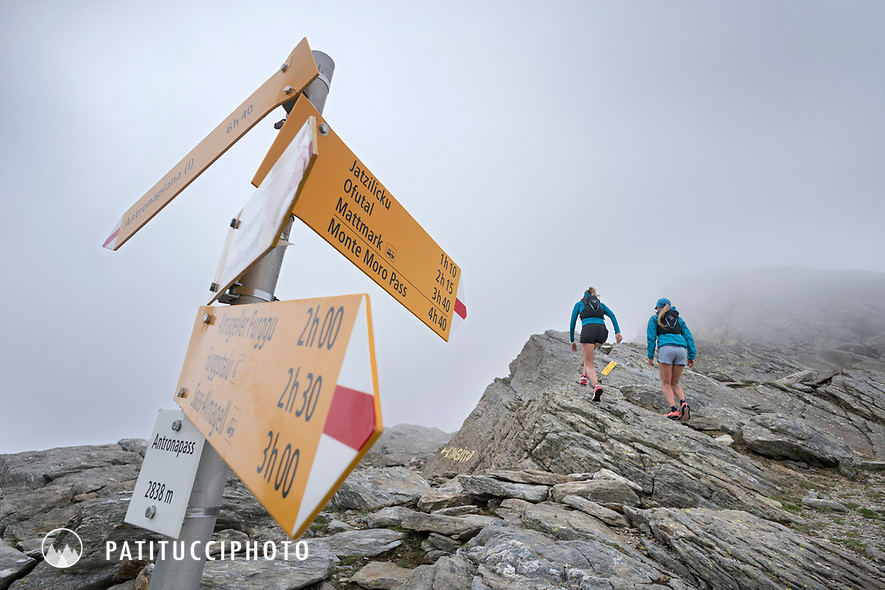Runners passing a trail sign in the fog on the Antronapass, above Saas Almagell, Switzerland.