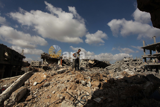 A Palestinian man reacts atop the remains of his destroyed house in the Shejaia neighbourhood, which witnesses said was heavily hit by Israeli shelling and air strikes during an Israeli offensive, in Gaza City July 26, 2014. A 12-hour humanitarian truce went into effect on Saturday after Israel and Palestinian militant groups in the Gaza Strip agreed to a U.N. request for a pause in fighting and efforts proceeded to secure a long-term ceasefire moved ahead. Photo by Ashraf Amra