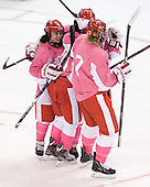 Taylor Holze (BU - 24), Isabel Menard (BU - 20), Jenn Wakefield (BU - 9) and Shannon Stoneburgh (BU - 7) celebrate Menard's goal. - The Boston University Terriers defeated the visiting Northeastern University Huskies 3-2 on Saturday, January 28, 2012, at Agganis Arena in Boston, Massachusetts.