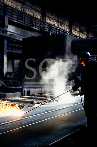 Sofia, Bulgaria. Old-fashioned steelworks; worker using electric arc to cut rolled steel sheets in Dickensian factory.