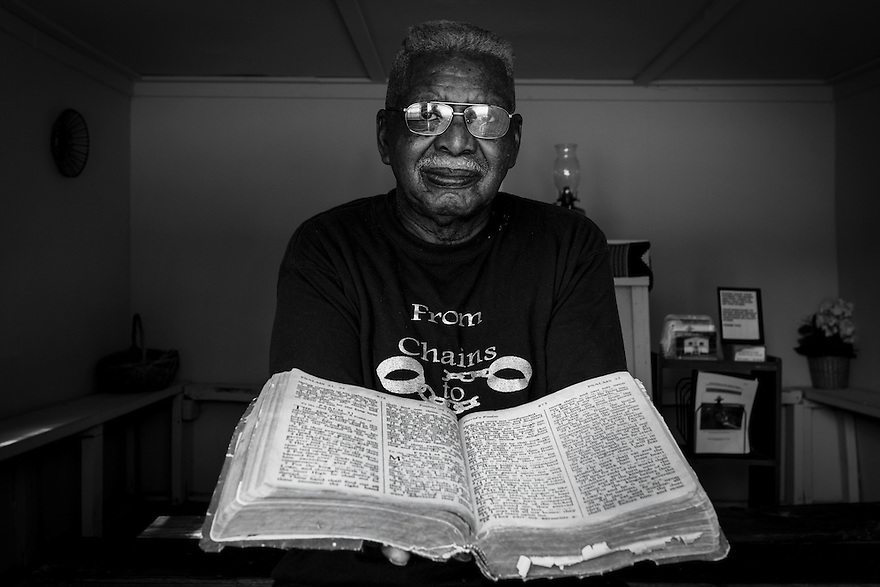 Robert Middleton, deacon at First African Baptist Church on St. Helena sits in the Coffin Point praise house with an old bible that has been used in the praise house for over 60 years.