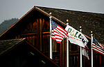 The PALCO corporate flag flies alongside the US and California flags over the Scotia, CA shopping center on Tuesday, June 27, 2006. The town of Scotia in Northern California is a company town owned by the Pacific Lumber Company (PALCO), but that will change as the company will begin to sell the town. (Photo by Max Whittaker for The New York Times)<br />