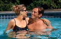 A married couple get romantic each others company in a swimming pool.