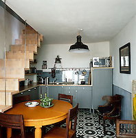 A kitchen/dining room with a staircase to one side in a converted Parisian apartment