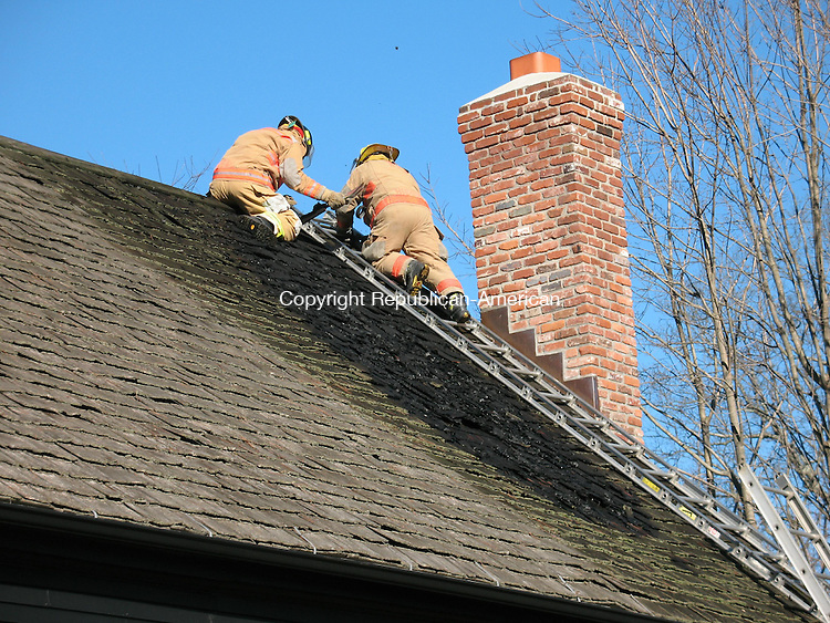 WOODBURY, CT - 19 November 2008 - 111908RH01 - Woodbury firefighters rip off shingles from the roof of a house on Main Street North to be sure no burning embers remain. Officials suspect an ember from the fireplace ignited a fire on the roof Wednesday before firefighters doused it.