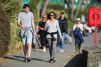 WEATHER PICTURE WALES<br /> A young man and lady take a stroll during the unusually warm weather in Langland Bay near Swansea, Wales, UK. Wednesday 27 February 2019