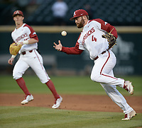 NWA Democrat-Gazette/ANDY SHUPE<br /> Arkansas second baseman Trevor Ezell fumbles the exchange while attempting a throw to first against Western Illinois Tuesday, March 12, 2019, during the second inning at Baum-Walker Stadium in Fayetteville. Visit nwadg.com/photos to see more photographs from the game.