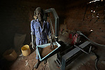 A man runs the grinding mill in Lugi, a village in the Nuba Mountains of Sudan. The area is controlled by the Sudan People's Liberation Movement-North, and frequently attacked by the military of Sudan. The mill is used by families to grind food grains like corn and sorghum.