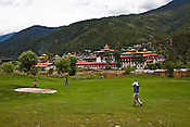 Local Bhutanese play golf at the Royal Thimphu Golf Course against the background of the Tashichho Dzong in Thimphu, Bhutan. Photo: Sanjit Das/Panos