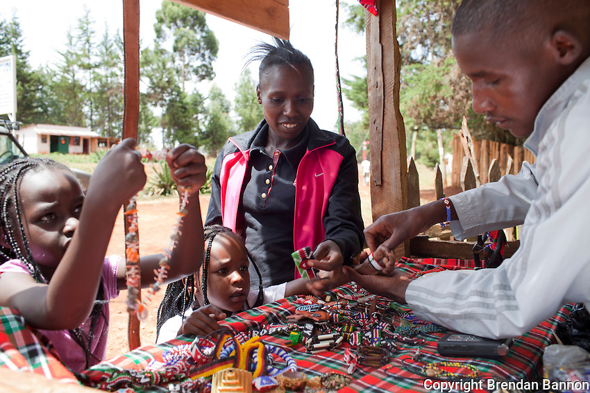 Florence Kiplagat and her children Faith, left, and Asha, center, shop for bracelets at Johanna Kariankei's Olympics Corner shop. Kariankei, an amatuer athlete, makes and sells Olympics themed Masai jewelry to support his training in Iten, Kenya.