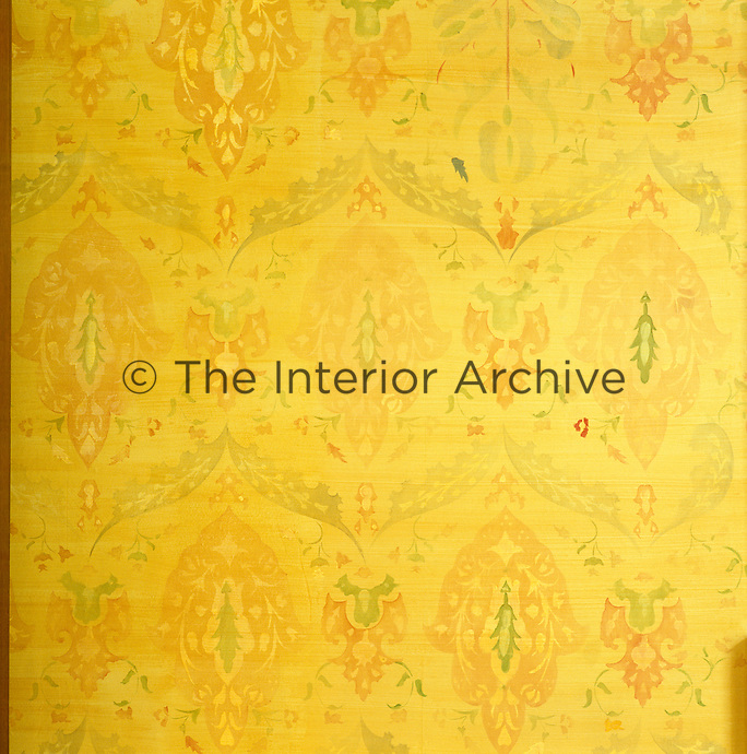 A detail of the yellow walls in a London living room highlighting the floral stencilled decoration
