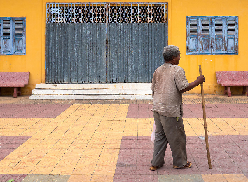 An old man walking through a Monastery in Battambang, wall colors and design, Cambodia.