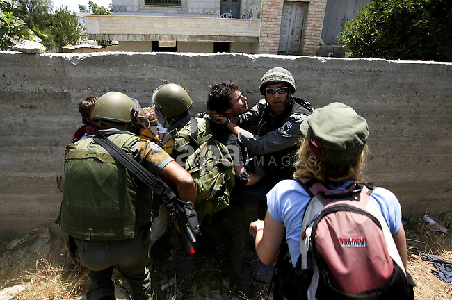 Israeli soldiers arrest a protester during a protest against the expansion of the Israeli settlements at Nabi Salah village near the West Bank City of Ramallah, on 09 July 2010. Photo by Eyad Jadallah