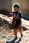 A girl in the village of Pir Zadeh in Maiwand district, Kandahar province, Afghanistan munches on cake given to her by soldiers of Company C, 2nd Battalion, 2nd Infantry Regiment. The soldiers were in the village to distribute food staples and winter clothing. They say such efforts help build rapport with villagers. Jan. 4, 2009. DREW BROWN/STARS AND STRIPES