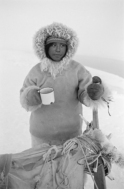 Otto Simigak with a mug of tea during a break on a hunting trip in light snow. Siorapaluk, Northwest Greenland.