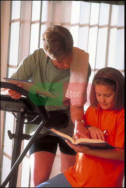 woman helps daughter with homework while exercising on treadmill