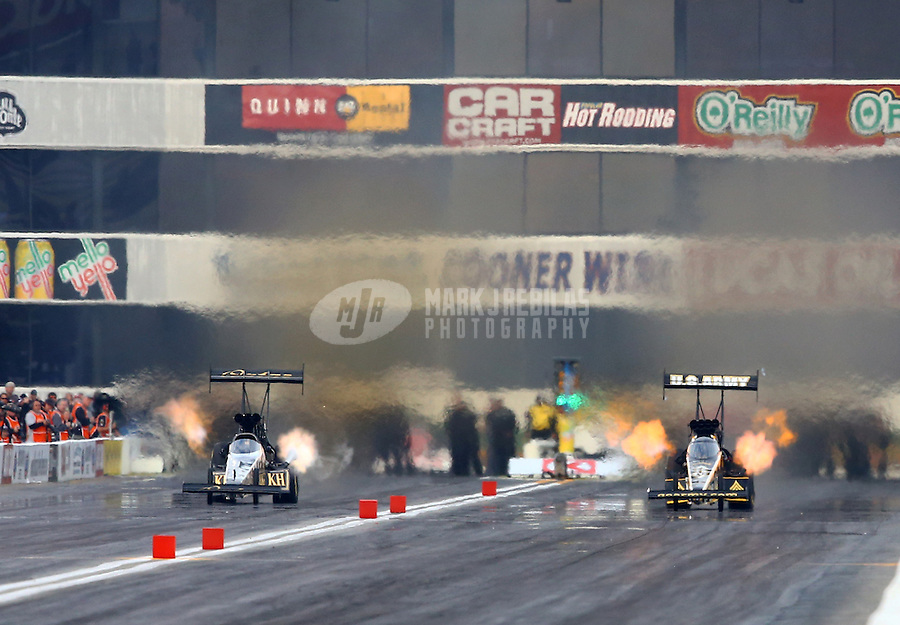 Feb 8, 2014; Pomona, CA, USA; NHRA top fuel dragster driver Khalid Albalooshi (left) races alongside Tony Schumacher during qualifying for the Winternationals at Auto Club Raceway at Pomona. Mandatory Credit: Mark J. Rebilas-