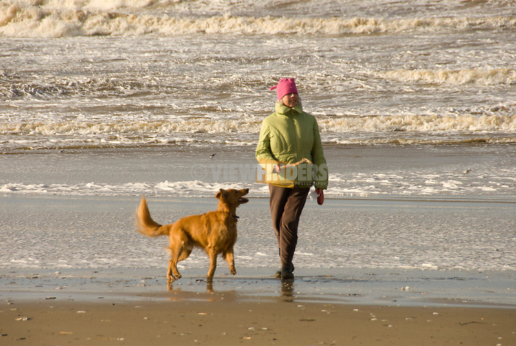 Woman with a Golden Retriever on the beach, Oregon Coast