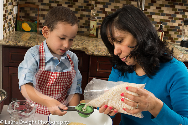 3 year old boy in kitchen at home with mother learning to cook baking, holding measuring cup as mother fills it with quinoa flakes