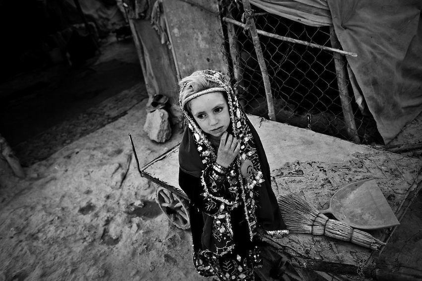 A displaced Afghan girl walks passed an open sewer in Chamane Babrak, a tented slum community for displaced Afghans just west of Kabul, Afghanistan, Monday, Oct 5, 2009. The majority of the familes in Chamane Babrak are returnees from Iran.