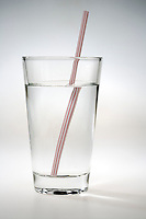 REFRACTION OF LIGHT - STRAW IN GLASS OF WATER (1 of 2)<br /> Refraction When Straw Enters Water at an Angle<br /> Light rays passing from one clear medium to another are refracted at the boundary between the two media.  The image of the straw is refracted by both the air-glass media and the glass-water media.