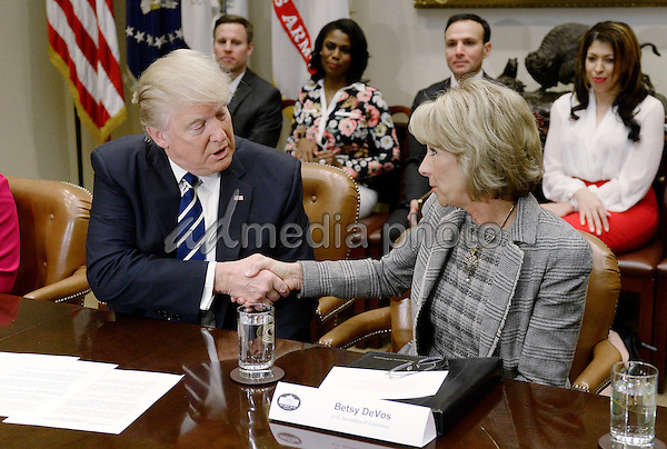 United States President Donald Trump congratulates Education Secretary Betsy DeVos  during  a parent-teacher conference listening session in the Roosevelt Room of the White House on February 14, 2017 in Washington, DC. Photo Credit: Olivier Douliery/CNP/AdMedia