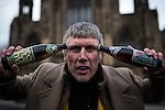 "© Joel Goodman - 07973 332324 .  12/01/2015 . Salford , UK . BEZ ( Mark Berry ) poses with "" Frack Free "" beer in front of Salford Cathedral at the launch of his parliamentary campaign for the constituency of Salford and Eccles at a poster site on Chapel Street , Salford . Bez , the freaky dancer from Madchester band The Happy Mondays , is standing for The Reality Party . Seat incumbent , Labour's Hazel Blears , is standing down at the 2015 election . Photo credit : Joel Goodman"