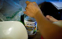 Wall Street Journal reporter Ana Campoy (cq) caps a bottle of apple cider vinegar, a crucial ingredient in pickling and canning, during a canning class at her home in Dallas, Texas, USA, Saturday, Sept. 12, 2009. Growing produce or buying locally grown vegetables and canning at home is a fun and healthy way to keep grocery costs down...CREDIT: Matt Nager for The Wall Street Journal