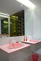 A pair of pink wash basins lines one wall of the shower room