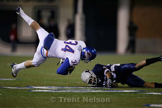 Boise State's Kirby Moore (left) flies through the air after colliding with Utah State's Curtis Marsh. Utah State vs. Boise State college football Friday, November 20 2009.