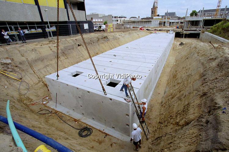 Foto: VidiPhoto..EDE - In het centrum Ede wordt deze week volop gewerkt aan een enorme ondergrondse badkuip. Het waterbassin is geschikt voor het opvangen van een half miljoen liter regenwater. De betonnen regenton moet onder meer voorkomen dat de ondergrondse garage in aanbouw tijdens hevige regenbuien volloopt. De put bestaat uit 29 betonelementen van 15.000 kilo. Vrijdag is de bak waterdicht.
