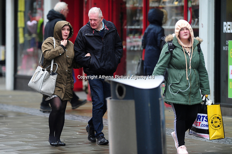 Pictured: A women and man walk as they battle with the wind and rain in Swansea City Centre, Swansea Wales, UK. Friday 08 February 2019<br /> Re: