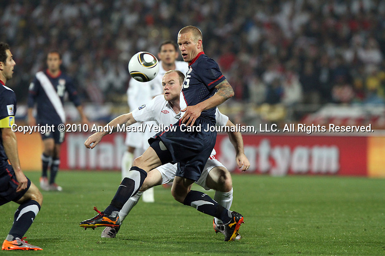 12 JUN 2010:  Jay DeMerit (USA)(15) and Wayne Rooney (ENG)(behind) compete for a loose ball.  The England National Team played the United States National Team played to a 1-1 tie at Royal Bafokeng Stadium in Rustenburg, South Africa in a 2010 FIFA World Cup Group C match.