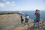Tourists taking photos Dún Aengus fort Inishmore, Aran Islands, County Clare, Ireland